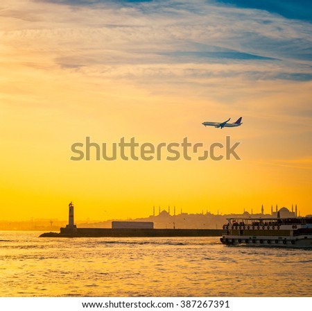 Sunset with silhouettes of mosque and lighthouse at seaside view of Istanbul. Panoramic cityscape of Istanbul with a ship and airplane. Travel to Istanbul on passenger transport in Turkey. - stock photo