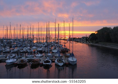 Sunset with silouetts of masts and reflections.