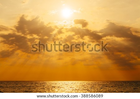 Sunset with sun rays and clouds, instagram toning - stock photo