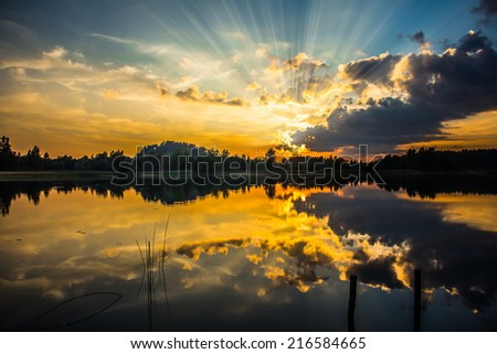 Sunset with sunbeams - stock photo