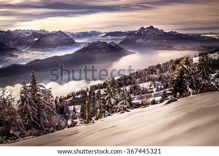 Sunset with view on distant mountains and valley with a lake and forest covered by snow in the cold winter  - stock photo