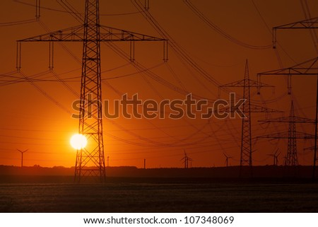 Sunset with Wind Turbines behind Power Lines and a group of Power Towers - stock photo