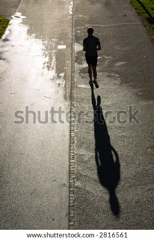 sunset workout, silhouette of runner, backlit with shadow - stock photo