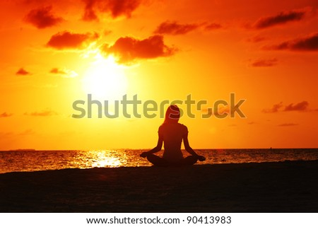 sunset yoga woman on sea coast - stock photo