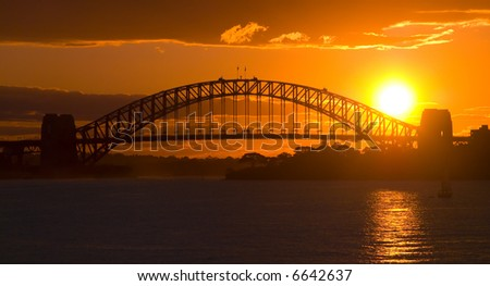 Sunsets behind Sydney Harbor ( Harbour ) Bridge - a deep golden orange sunset