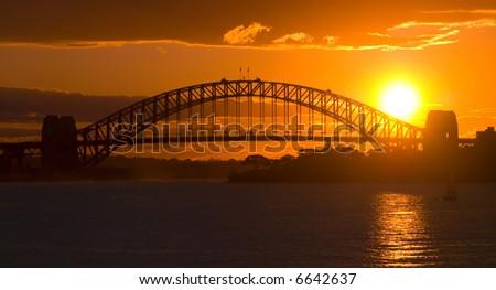 Sunsets behind Sydney Harbor ( Harbour ) Bridge - a deep golden orange sunset - stock photo