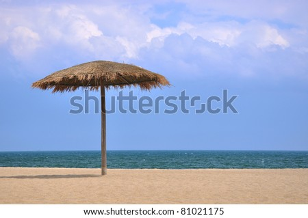 Sunshade on beach with blue sky and white cloud - stock photo