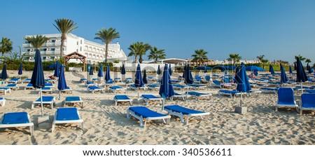 Sunshade umbrellas and deckchairs on the beautiful beach, Cyprus - stock photo