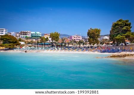 Sunshade umbrellas and deckchairs on the beautiful Ksamil beach, Albania. - stock photo