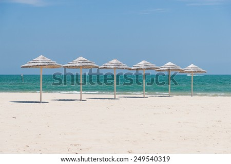 Sunshade Umbrellas on the beach at summer day - stock photo