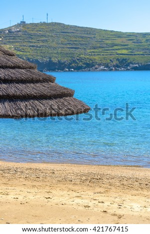 Sunshade umbrellas on the beach during a sunny summer day in Mykonos, Greece. - stock photo