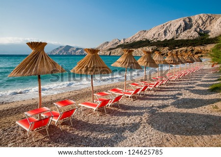 Sunshades and orange deck chairs on beach at Baska - Krk - Croatia - stock photo