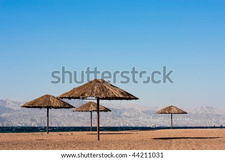 Sunshades near on beach of the Read Sea in Aqaba, Jordan. City of Eilat, Egypt in background. - stock photo