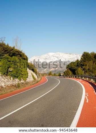 Sunshine on ann icy road through snowcaped landscape - stock photo