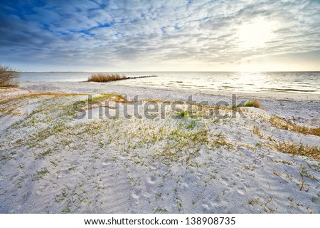 sunshine over sand dunes on the beach by North sea, Netherlands - stock photo