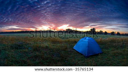 Sunshine rising over a tent in the wilderness - stock photo