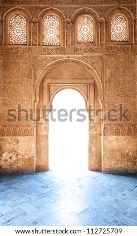 Sunshine through door to Granada palace. Sunlight on blue floor. Stone wall and windows in arabesque design. Ornate pattern of building in arabic style. Famous tourist destination in Spain, Europe. - stock photo