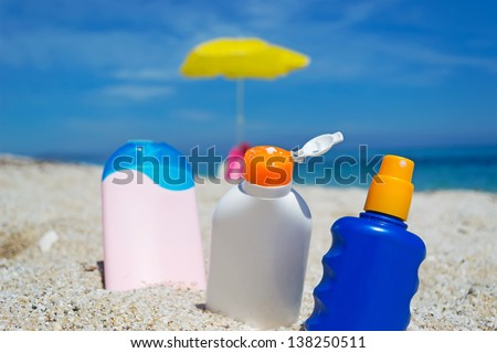 suntan lotion bottles in the sand - stock photo
