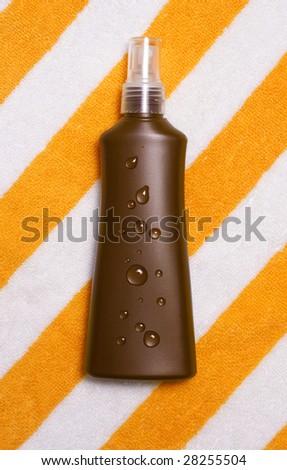 suntan lotion container on beach towel - stock photo