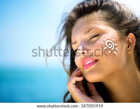 Suntan Lotion Woman Applying Sunscreen Solar Cream. Beautiful happy cute Girl applying Sun Tan Cream on her Face over ocean background. Sun Tanning. Skin care and Protection. Vacation - stock photo