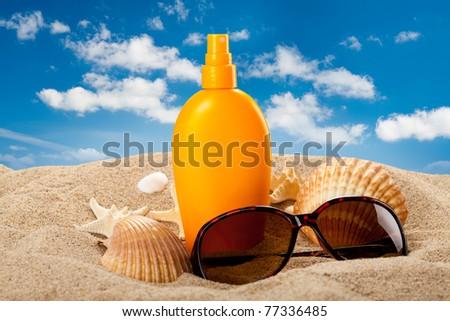 Suntan oil and dark glasses on the beach - stock photo