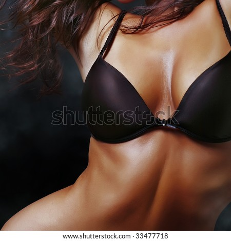 Suntanned beautiful harmonous well-groomed body of the young girl in a brassiere, close up - stock photo
