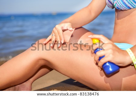 suntanning, woman applying sun protection lotion on leg for skincare, sea in background