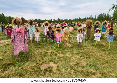 SUOMUSSALMI, FINLAND - JULY 13, 2014: Quiet  people is work of art by artist Reijo Kela. About thousand figures, which  without clothes would merely be a thousand standing wooden crosses on a field. - stock photo