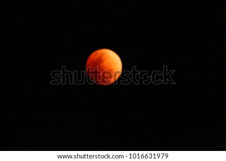 Super blue blood moon with total lunar eclipse over dark sky background