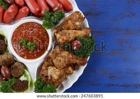 Super Bowl Sunday football party celebration food platter with chicken buffalo wings, meat balls, hot dogs and salsa dip on blue wood table. - stock photo