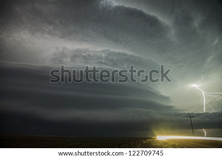Super-cell thunderstorm with lightning & oncoming headlights - stock photo