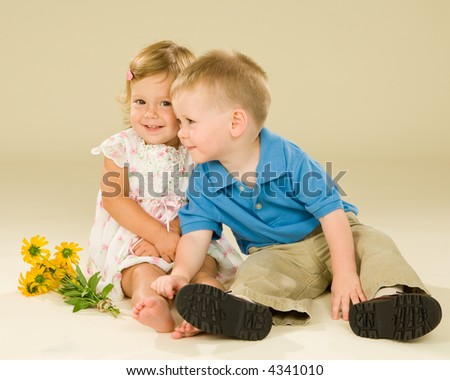 "Super cute baby ""couple"" having an embrace and exchanging a bouquet of yellow flowers. Cream colored background. - stock photo"