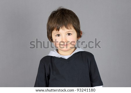 Super cute little boy preschooler with big brown eyes and a charming hint of a smile over grey background.