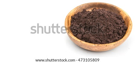 Super food dried maqui berry powder in wooden bowl over white background