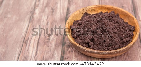 Super food dried maqui berry powder in wooden bowl over wooden background