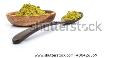 Super food moringa powder in wooden bowl and wooden spoon over white background