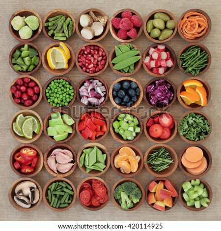 Super food sampler for paleolithic diet with fresh vegetables and fruit in wooden bowls over brown paper background. High in vitamins, antioxidants, minerals and anthocyanins. - stock photo