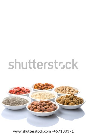 Super food tiger nuts, mulberry berries, cacao beans, goji berries, quinoa seeds, chia seeds, golden berry in white bowls over white background