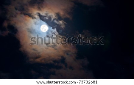 "Super full moon shining through the clouds.  Taken 3-19-11 in Hawaii, this full moon is rare as it is closest to the earth as it has been in 18 yrs.. Astronomers call this one ""The Super Full Moon"" - stock photo"