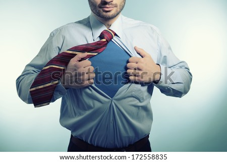Super hero. Business man opening his shirt like a superhero, over blue background - stock photo