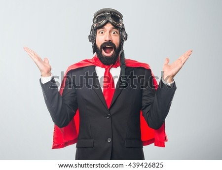 Super hero businessman doing surprise gesture over grey background
