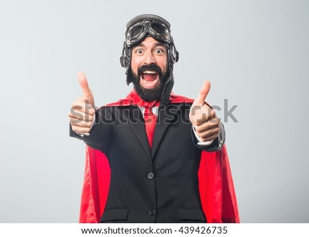 Super hero businessman with thumb up over grey background