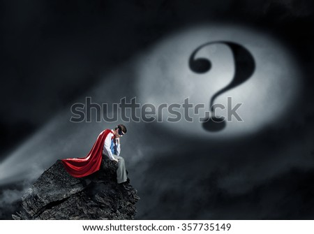 Super hero deep in his thoughts - stock photo