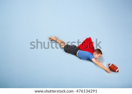 Super hero football kid wearing a cape and diving for a catch