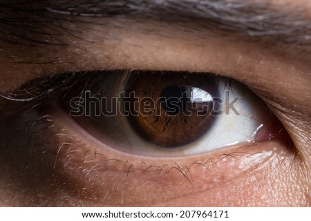 super macro shot of asian male's eye. Texture of the dark eye is visible - stock photo