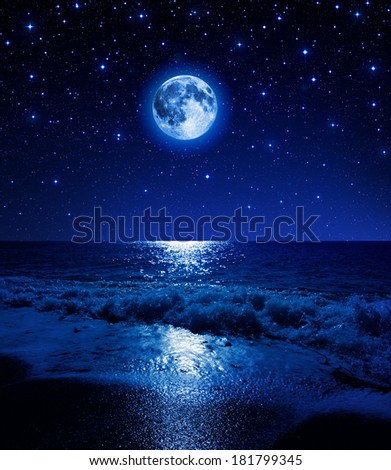 super moon in starry sky on sea beach - stock photo