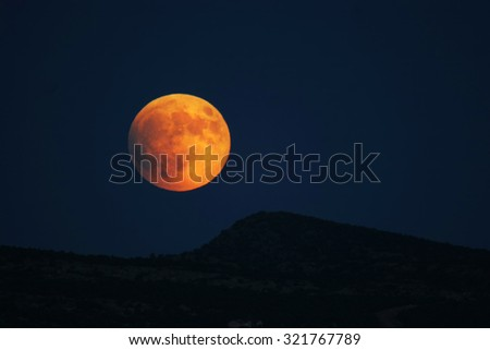 Super moon rising over hills prior to full eclipse - stock photo