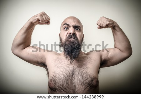 super power angry muscle bearded man  on gray background - stock photo