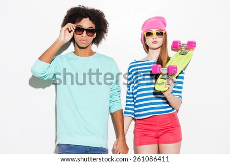 Super styling and in love. Funky young couple wearing eyewear and posing against white background - stock photo