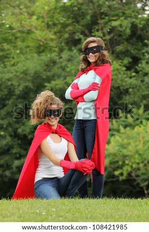 Super team of super heroes girl with red cape and red gloves outside in a forest